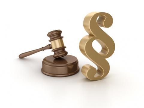 A képen bírói kalapács és paragrafus jel látható.